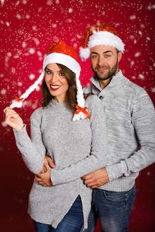 Couple dressed with winter clothes and santa hat