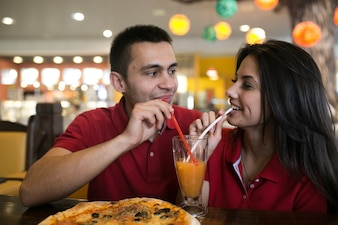 Couple drinking from one glass