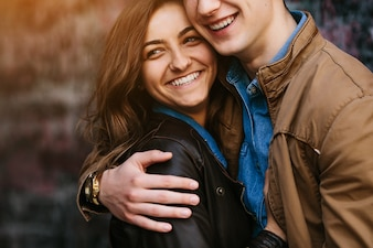 Couple embracing on the street with a brick wall background