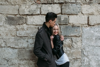 Couple embracing with a large brick wall behind