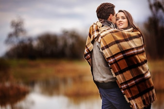 Couple hugged and covered by a blanket