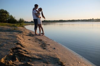 Couple hugging with lake background