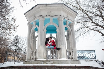 Couple in stone pavilion in winter