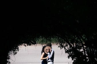 Couple kissing and covering themselves with a hat
