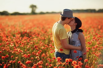 Couple kissing in a field of red flowers