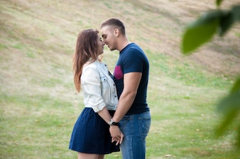 Couple kissing in a green field