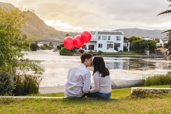 Couple kissing in a park with red balloons