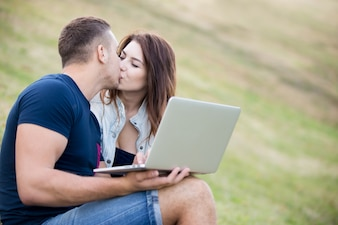 Couple kissing in the grass with a laptop