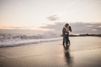 Couple kissing on the shore of the beach at sunset