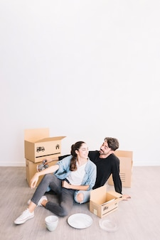 Couple leaning against moving boxes