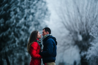 Couple looking closely at eyes with blurred snowy background