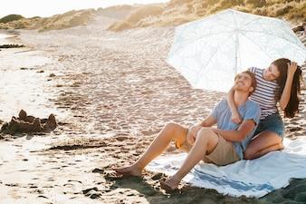 ビーチでタオルでくつろぐカップル