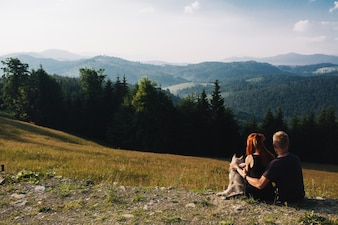 Couple sitting on a green field looking at nature