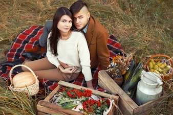 Couple sitting on the grass with boxes of vegetables