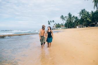 砂の海岸を歩いているカップル