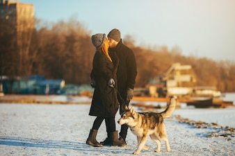Couple walking their dog while they kiss