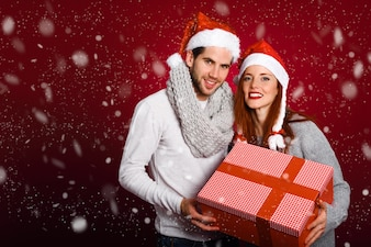 Couple with a christmas gift dressed with winter clothes and santa hat under snow on red background