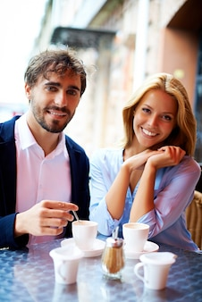 Couple with cup of coffee outside the cafe