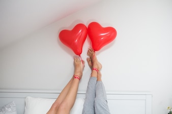 Couple with feet on the wall and holding a balloon with his foot