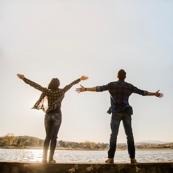 Couple with open arms enjoying nature