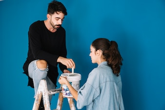 Couple with paint on ladder