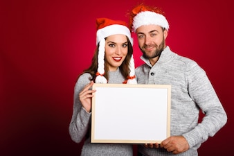 Couple with santa's hat holding blank board