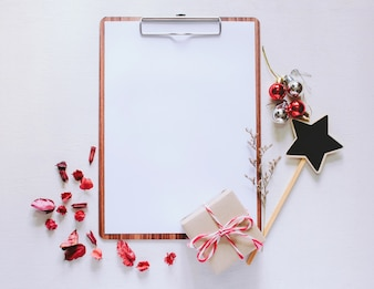 Craft and notebook mock up clipboard with christmas ornaments on white wood background