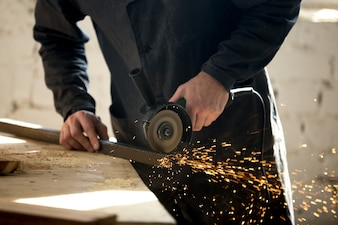 Craftsman working with electric tool in workshop