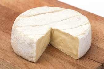 Creamy Brie on rustic wooden background, top view