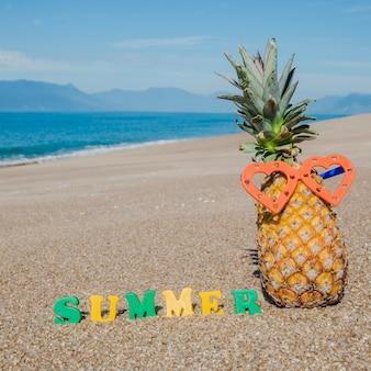 Creative arrangement of pineapple on sand