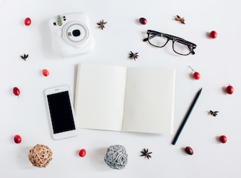 Creative flat lay of blank notebook, smartphone, instant camera with autumn ornaments on white background, top view