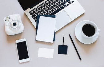 Creative flat lay photo of workspace desk with laptop, blank card, coffee, tag, smartphone and camera on grey background