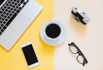 Creative flat lay photo of workspace desk with laptop, smartphone, coffee, eyeglasses and film camera on yellow modern background