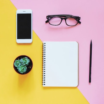 Creative flat lay photo of workspace desk with smartphone, eyeglasses, cactus and notebook with copy space background, minimal style