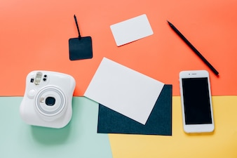 Creative flat lay style of workspace desk with instant camera, smartphone, blank card, tag and pencil on minimal color background