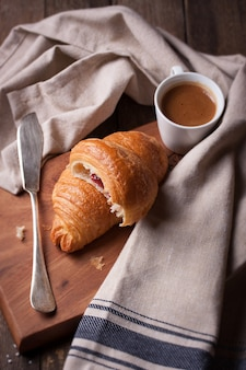 Croissant next to a knife and a cup of coffee