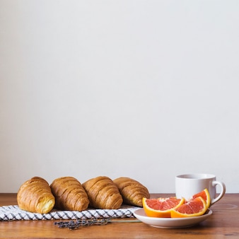Croissants with oranges and cup