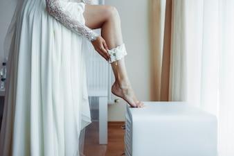 Crop bride putting on garter