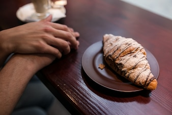 Crop couple holding hands near croissant