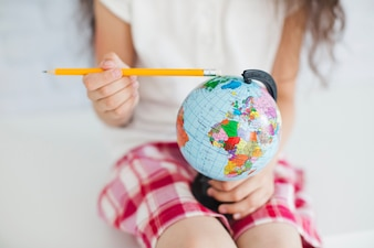 Crop girl with pencil and globe