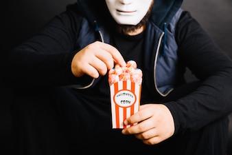 Crop man in mask eating popcorn