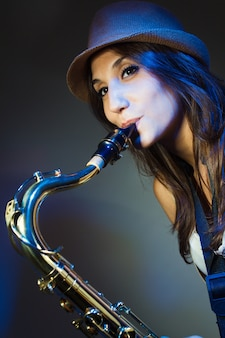 Crop photo of female playing on sax