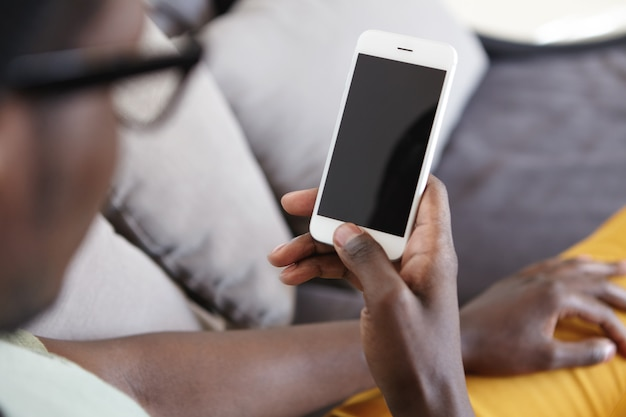 Cropped indoor image of unrecognizable dark-skinned man relaxing on couch in living room, using home wi-fi on modern mobile phone