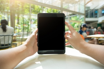 Cropped shot view of woman's hands holding tablet with blank copy space screen for your text message or information content, female reading text message on notepad during in urban setting