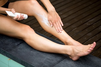 Cropped View of Woman Applying Sunblock on Legs