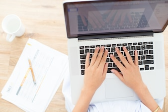 Cropped View of Woman Hands Typing on Laptop