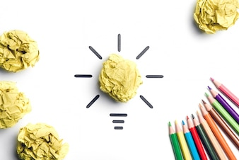 Crumpled paper light bulb and colored pencils. Metaphor for good idea. Inspiration concept