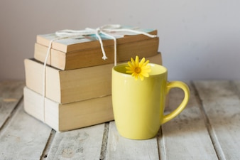 Cup next to pile of book