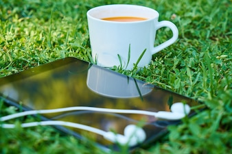 Cup of coffee next to a mobile with headphones