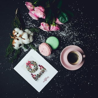 Cup of coffee stands on black table with macaroons and roses